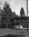View of portion of building, truck and man. Trees in background. See 02-137