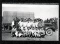 Crew of young men posed in front of truck